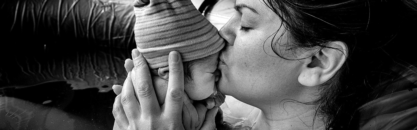 A woman in a birthing pool holds her new born baby, her eyes are closed and she is kissing its forehead tenderly. The baby is wearing a stripy knitted hat.
